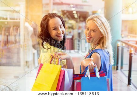 Two happy and cheerful  best friends shopping together