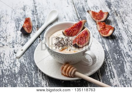 yogurt with pieces of fig chia seeds honey in a white cup on a wooden background