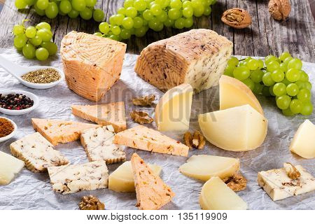 organic homemade goat cheese with walnuts and spices on a parchment paper. Green Grapes and walnuts on an old rustic background studio lights close-up