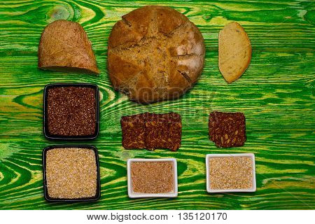 Loaf of homemade bread slices flax seeds and organic grain in bowls on green wooden background
