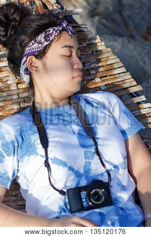 Young asian woman blue and white shirt sleeping at big cradle bamboo soft focus