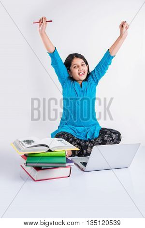 ute little indian girl studying on laptop, asian small girl studying and using laptop, innocent indian girl child and study concept with pile of books & laptop
