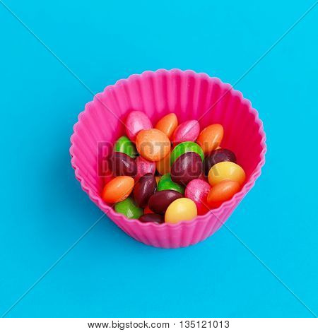 Colorful candies in cupcake case on the blue background
