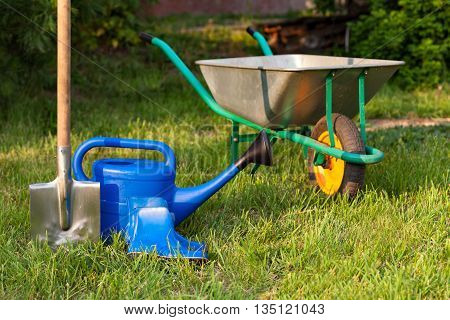 Blue watering can and rubber boots on a background of green lawn. Bright inventory gardener. Trolley and shovel for the garden care..