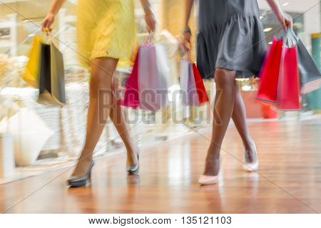 Two women shopping together in shopping together, blur