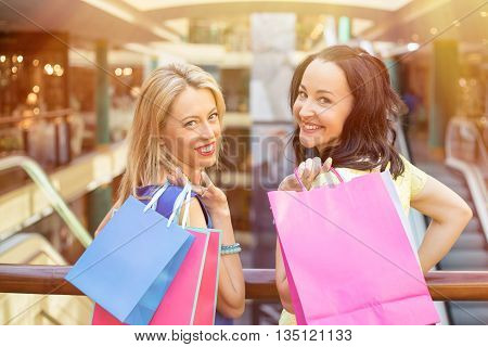 Portrait of two friends with shopping bags