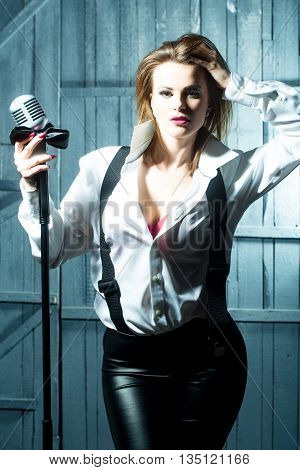 young pretty woman with sexy red lips singing into silver studio microphone in retro braces and shirt holding bow