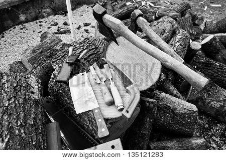 Two Axes In Stumps With Wood Working Tools Background Chopped Firewood. Black And White Photo