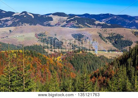 Carpathian Mountains Autumnal Panorama Fir Pine Forest with some Aspen and Birches Bright Autumnal Colors Local Village Making Column of Smoke