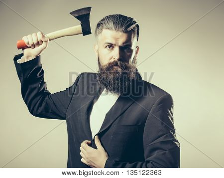 Handsome young man with long beard and moustache in black jacket holding sharp axe in studio on grey background