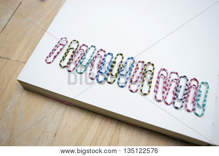 a row of clips on a notebook and wood background