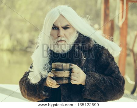 Druid old man with long grey hair and beard in fur coat with wooden mug in hands on blurred background
