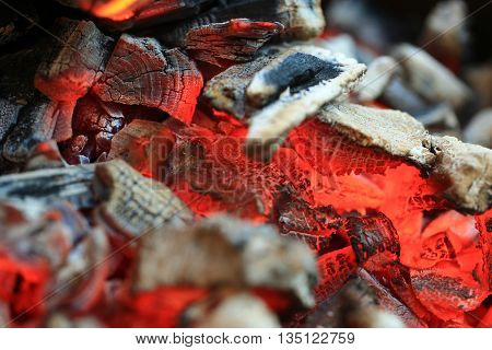 open fire with hot ash and charcoal burning with bright orange flame as abstract background
