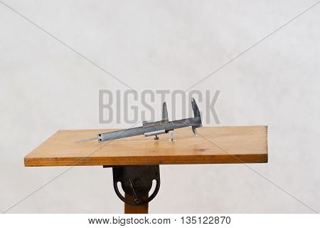 Different construction tools on a wooden background - screwdriver, caliper. Top view.