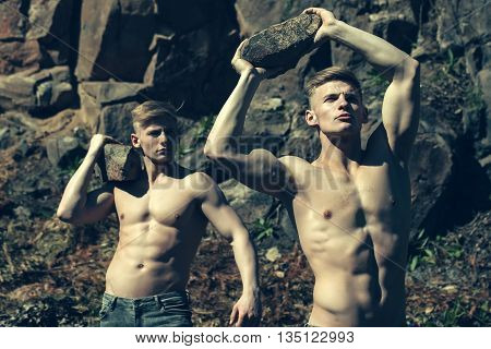 Men bare-chested young pose twin brother sexy models in jeans outdoor on mural background
