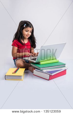 cute little indian girl studying on laptop, asian small girl studying and using laptop, innocent indian girl child and study concept with pile of books & laptop