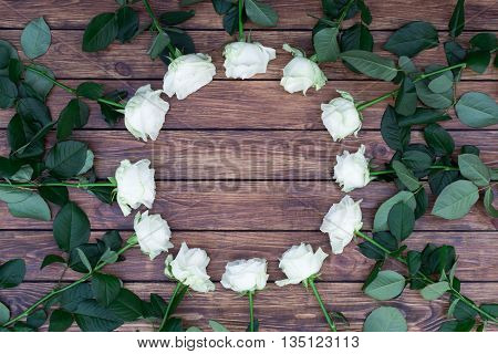 circle of white roses with green leaves on a background of brown wood planks with a place for an inscription