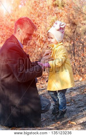 Father Helping Little Baby Daughter to Wear Coat on Walk in Autumnal Park Sun Shining Background