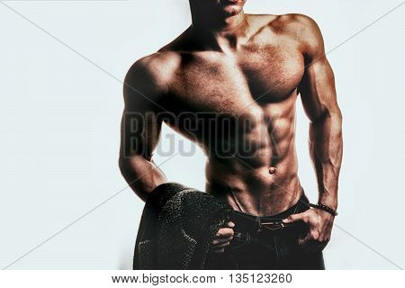Sexy muscular male torso of athlete bodybuilder posing in power with veins on hands and bare chest holding shirt on white background