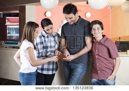 Boy Standing By Family Choosing Ice Cream From Menu