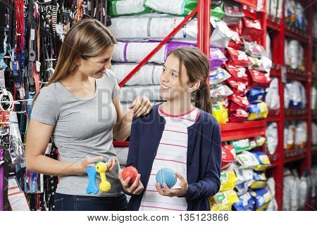Mother And Daughter Buying Toys In Pet Store