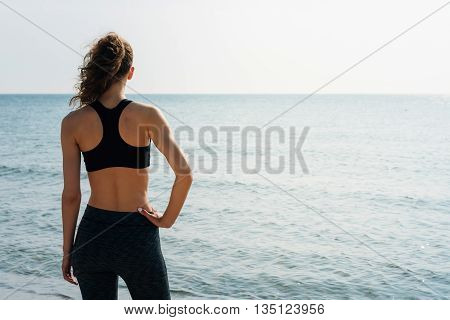 Sporty Girl With Curly Hair In A Sports Bra Standing On The Beach And Looking At The Sea In The Morn