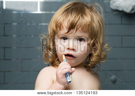 Small cute funny baby boy with blonde wet hair in bath cleaninng teeth with brush