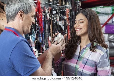 Salesman And Female Customer Playing With Guinea Pig