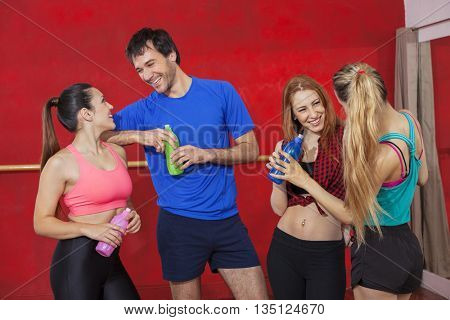 Smiling Zumba Dancers Holding Water Bottles In Gym