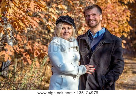 Husband and Wife Embracing Staying on Forest Alley with Bright Fall Colors Leaves Background