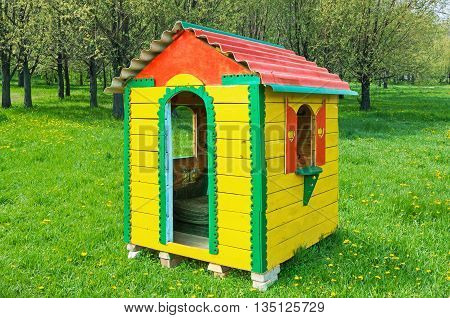 A small children's playhouse on the lawn in the city park in early spring
