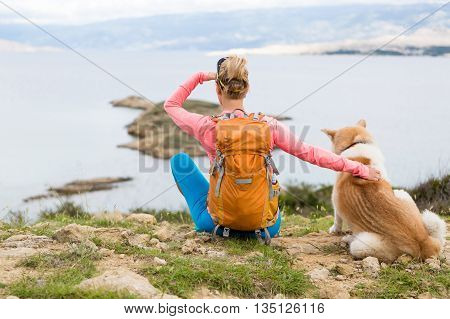 Woman hiking with akita inu dog looking at sea and mountains view. Recreation and healthy lifestyle outdoors in summer nature. Beautiful inspirational landscape. Trekking and activity concept.