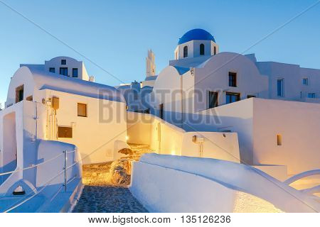 The traditional architecture of Santorini and the view of the white Greek church at sunset.