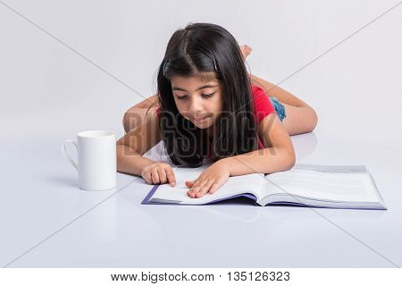 indian small girl reading book, asian girl child reading book over white background, cute 5 year old indian small girl reading book with milk mug