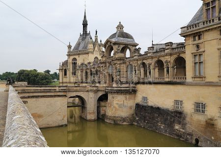 CHANTILLY, FRANCE - MAY 14, 2015: This is bridge over the moat and the entrance to the gates of the castle Chantilly.