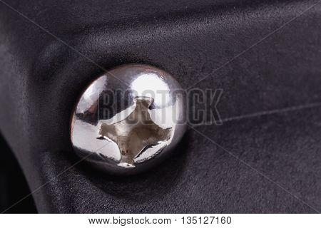 Single metal bolt head on a black plastic surface