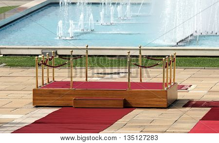 Red carpet with podium and two rope barriers