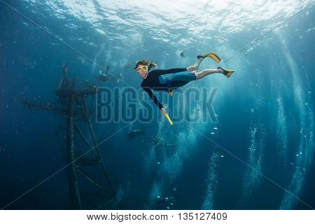 The underwater scenes. Lady the diver swims underwater by sunken ship