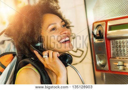 Portrait of smiling woman using telephone booth