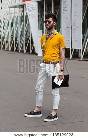 MILAN ITALY - JUNE 18: Fashionable man poses outside Jil Sander fashion show building for Milan Men's Fashion Week on JUNE 18 2016 in Milan.