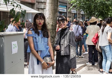 MILAN ITALY - JUNE 18: Two fashionable women pose outside Jil Sander fashion show building for Milan Men's Fashion Week on JUNE 18 2016 in Milan.