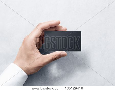 Hand hold blank plain black business card design mockup. Clear calling card mock up template holding arm. Visit pasteboard paper surface display front. Check small offset card print. Business branding