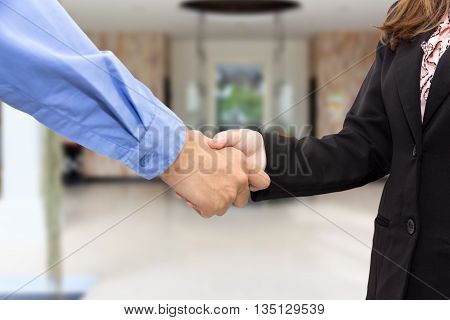 Close up of businessman and businesswoman shaking hands in waiting room.