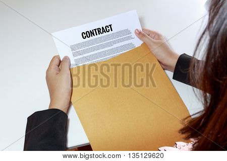 Woman hands holding contract document in envelope.