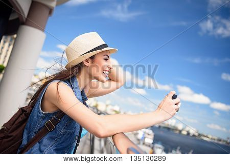 Carefree young woman is photographing rive scenery in city. She is standing and touching her hat. Girl is smiling happily