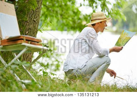 Happy senior woman painting picture in nature in summer