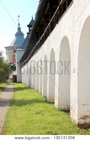 Arcade of the ancient courtyard of Spaso-Prilutsky Monastery at summer sunny day in in the Vologda Russia. Blue sky and green grass. Castle defense wall