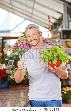 Happy gardener in garden center with plant (philodendron cordatum) holding his thumbs up