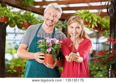 Two happy employees in a garden center with flower and seedling