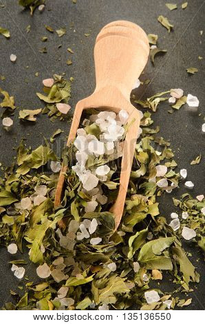sea salt mix with dried and shredded basil and wooden spoon